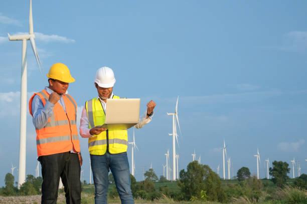 Turbina eólica asiática ingeniero mecánico equipo exitoso trabajo por computadora portátil en el campo de turbina eólica, energía eólica y concepto de energía alternativa, industria de energía eléctrica - foto de stock