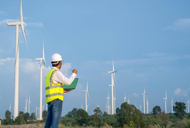 Wind Turbine Ingeniero Mecánico Asiático trabajando por computadora portátil en el campo de la turbina eólica, la energía eólica y el concepto de energía alternativa, industria de energía eléctrica.éxito pose feliz - foto de stock