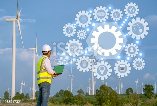 istock Wind Turbine Asian Mechanical Engineer working by laptop computer at Wind Turbine field,wind power and Alternative energy concept,Electric power industry, 1163517321