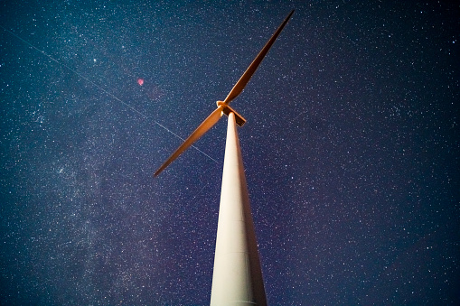 Wind turbine at night with star background, SK, Canada.