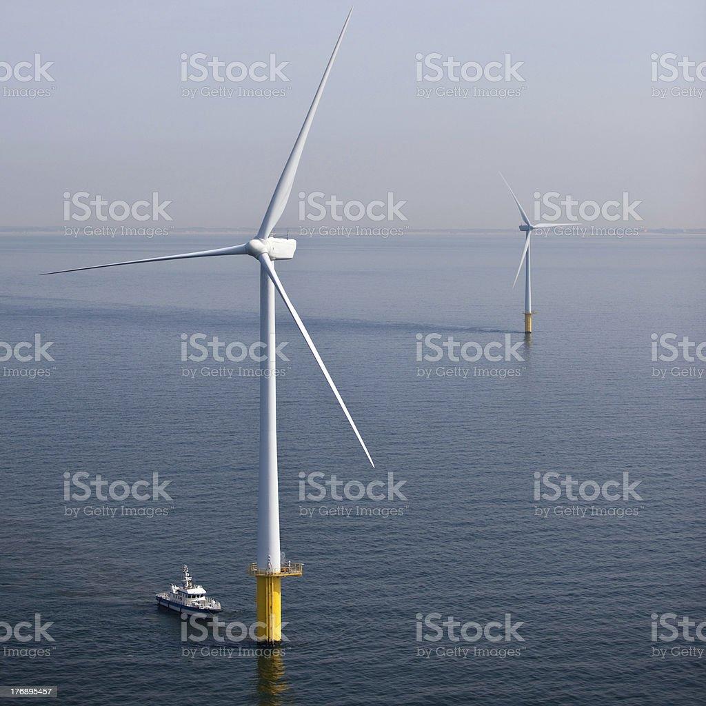 Wind turbine at sea during maintenance stock photo