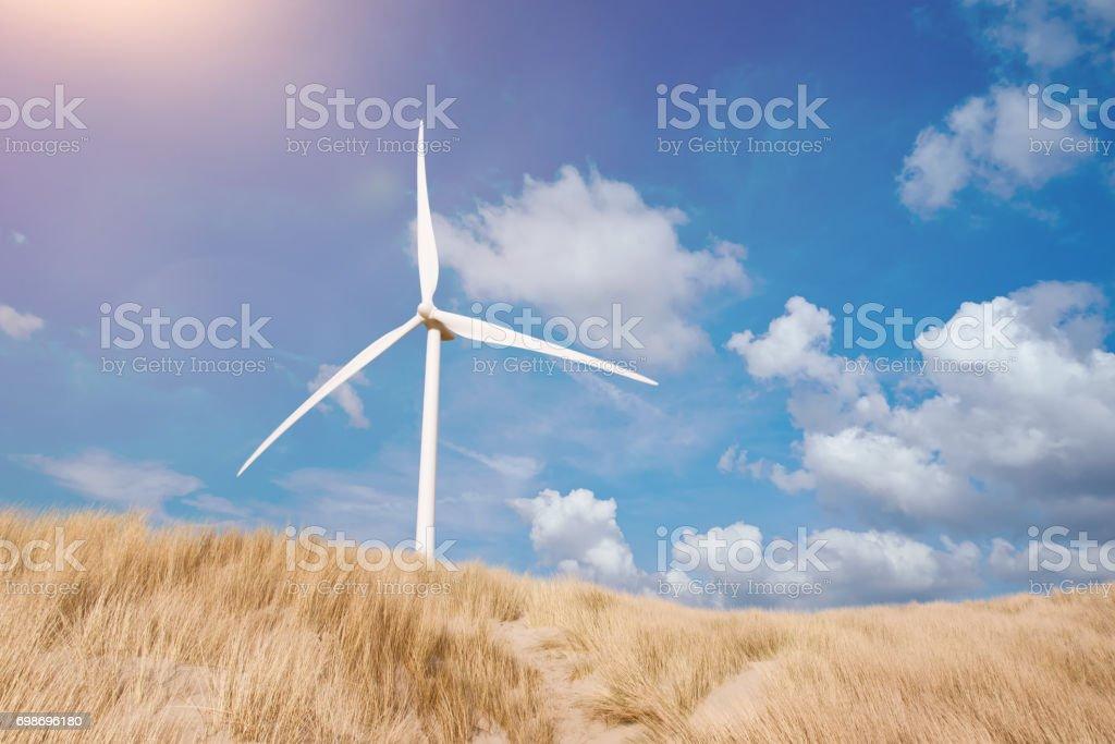 Windturbine hinter Dünen bedeckt mit Dünengebieten Grass unter blauen Sommerhimmel – Foto
