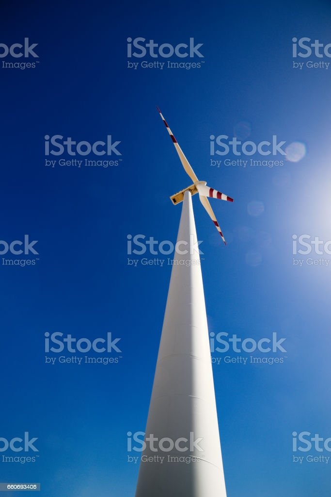 Wind turbine with dramatic blue sky and lens flare - portrait mode