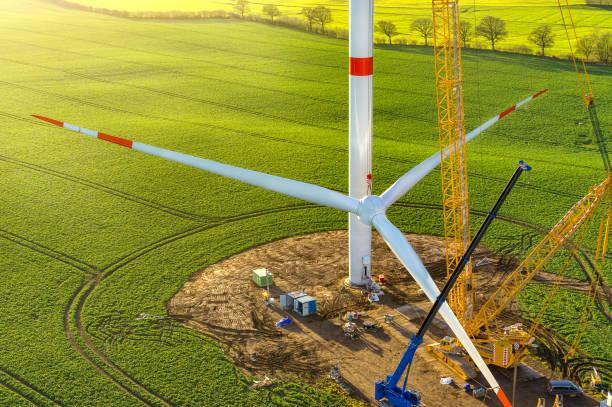 windkraftanlage errichtet sonnenaufgang - tim siegert stock-fotos und bilder