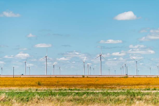 Gerador de exploração agrícola da turbina de vento perto de Roscoe ou Sweetwater Texas nos EUA na pradaria com fileiras de muitas máquinas para a energia - foto de acervo