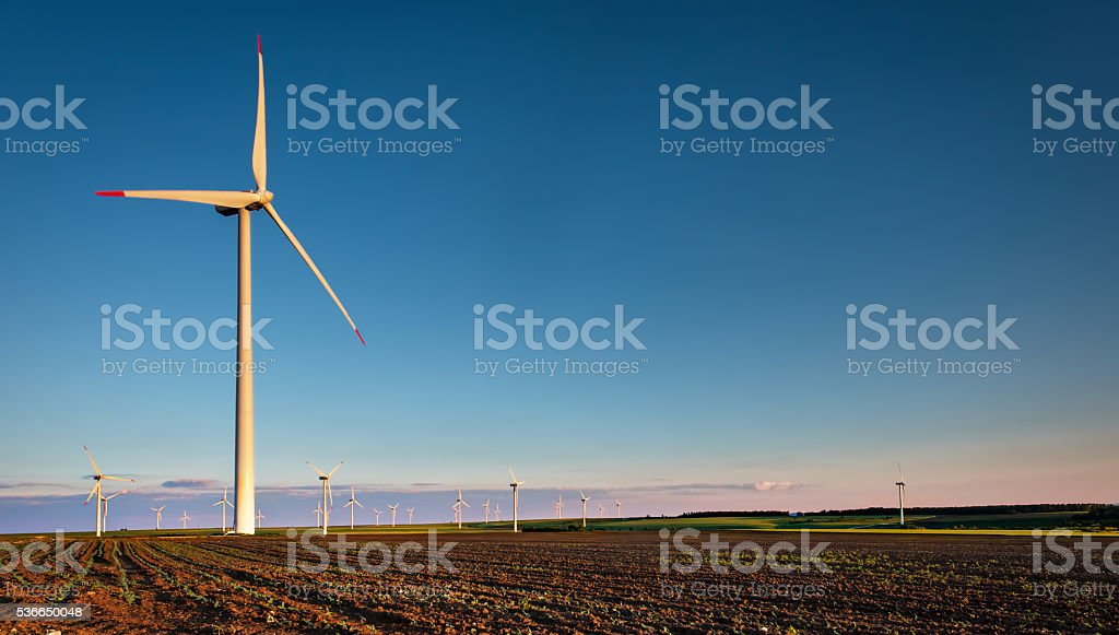 Wind turbine farm with rays of light at sunset. stock photo