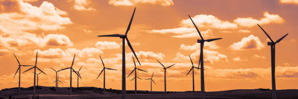 wind turbine veld bij zonsondergang, dramatische hemel - krachtapparatuur stockfoto's en -beelden