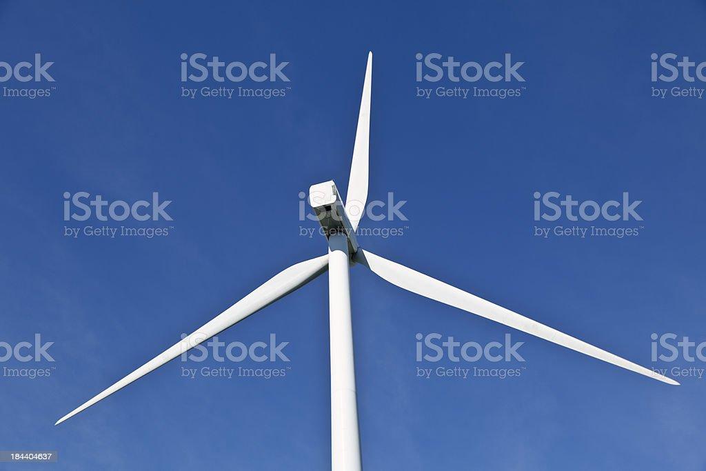 Wind Turbine in Sunshine Under Clear Blue Sky stock photo
