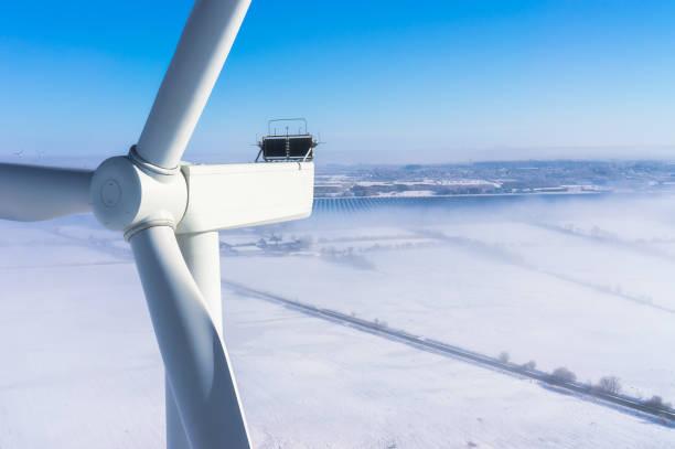 windkraftanlage im winter mit schnee und nebel luftbild und nahansicht - tim siegert stock-fotos und bilder