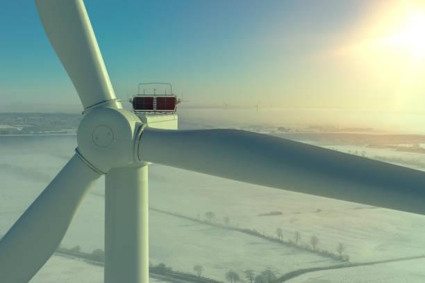 windkraftanlage im winter mit schnee und nebel in hintergrundbeleuchtung luftbild und nahansicht - tim siegert stock-fotos und bilder