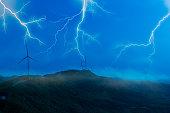 wind turbine on mountain top at night in storm lightning.