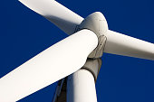 A white wind turbine isolated against a blue sky background