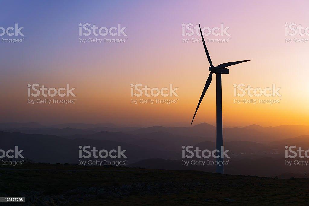 Turbina de viento en la puesta de sol en las montañas de silhouette - foto de stock