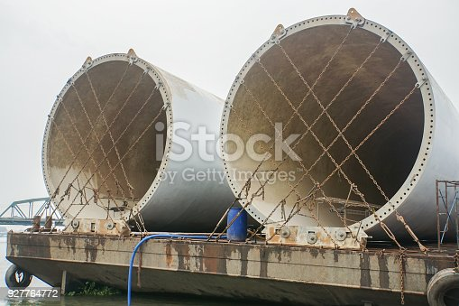 istock wind turbine tower secured with chains on barge for sea transport 927764772