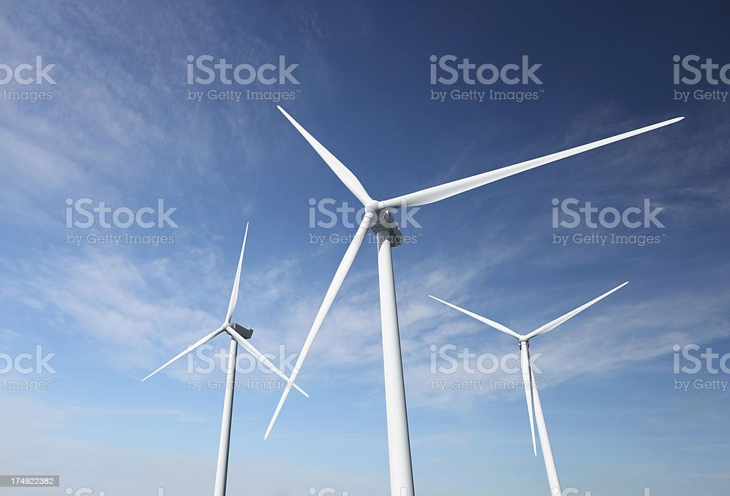 Wind turbines against an almost clear blue sky royalty-free stock photo
