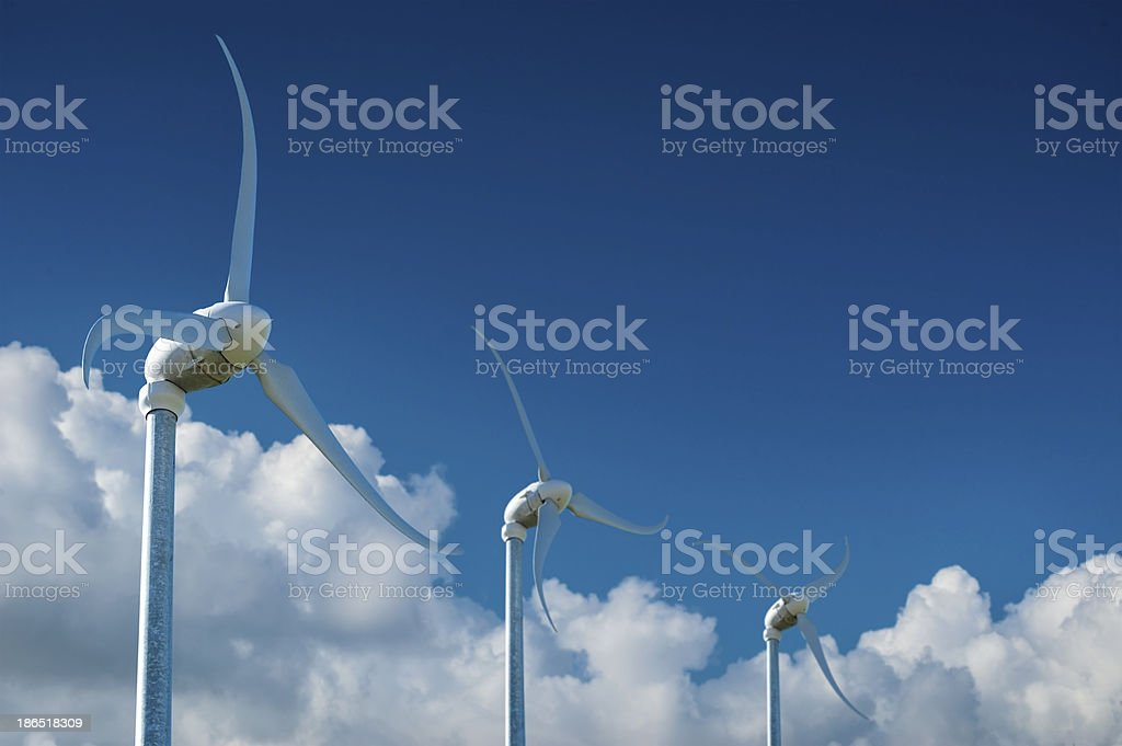 Wind turbines against blue sky with clouds royalty-free stock photo