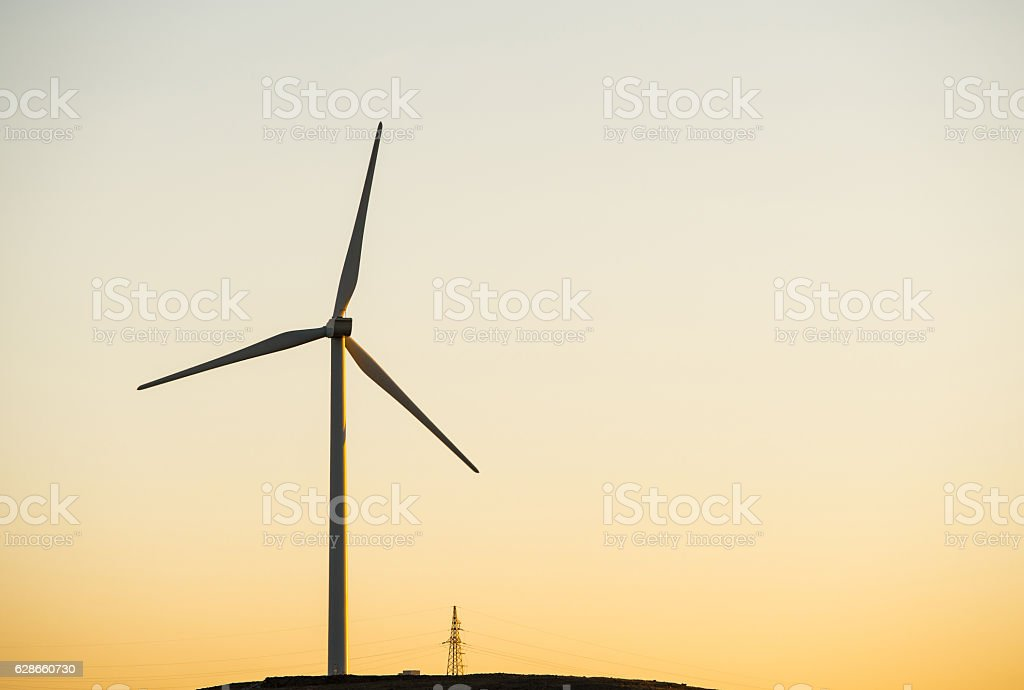 wind turbines against red and orange sunset stock photo