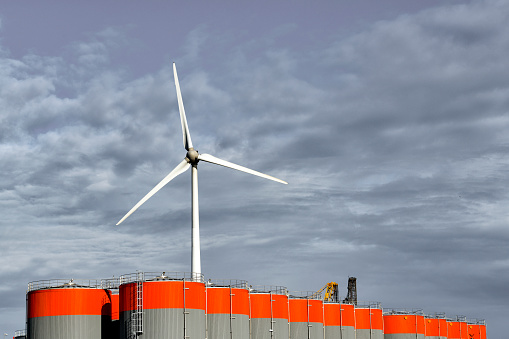 Wind turbines and large oil storage tanks in an industrial area with a blue sky in fluffy white clouds in the background.
