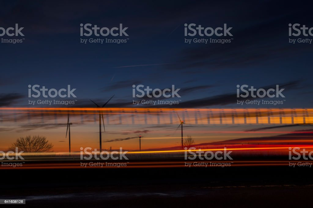 Wind turbines and light trails stock photo