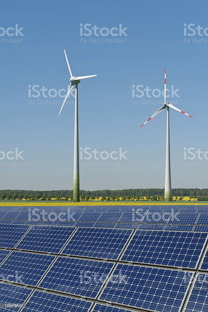 Wind turbines and solar panels against a rapeseed field stock photo