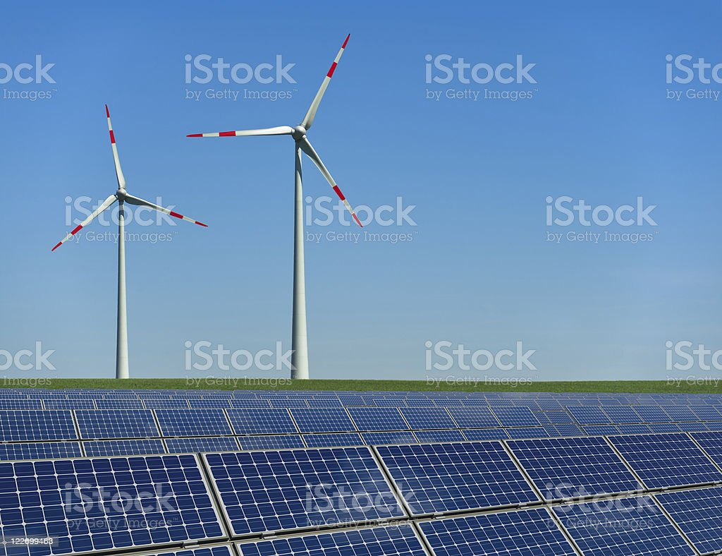 Wind turbines and solar panels in a field stock photo