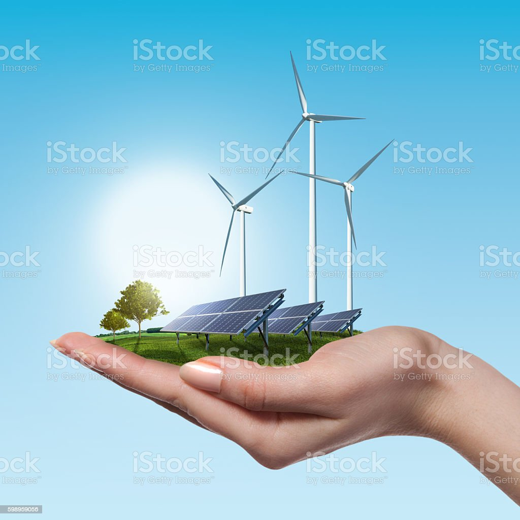 Wind turbines and solar panels in female hand - foto de stock