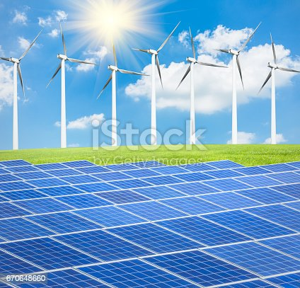 istock Wind turbines and solar panels on green field 670648660
