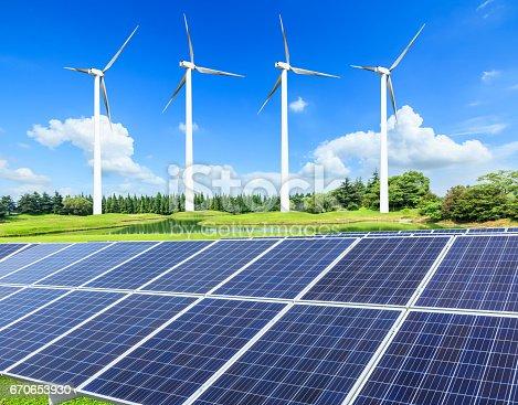 istock Wind turbines and solar panels on green field 670653930
