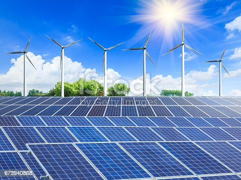 istock Wind turbines and solar panels on green field 673940868