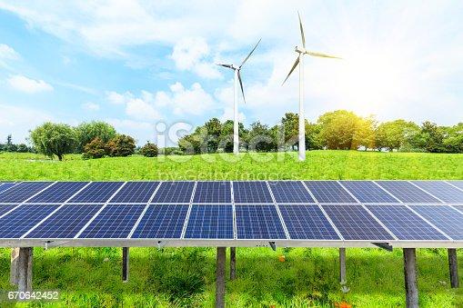 istock Wind turbines and solar panels on green grass 670642452