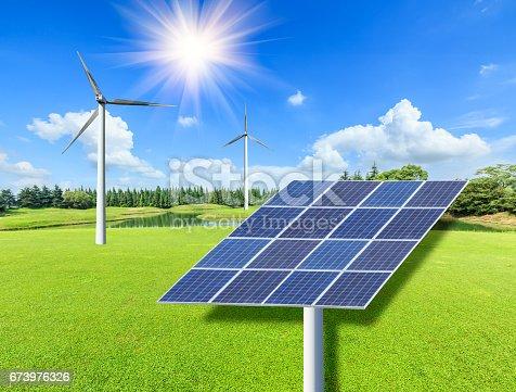 istock Wind turbines and solar panels on green grass 673976326