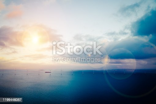 Aerial drone shot of of coastal wind turbines at a wind farm at the sea of Copenhagen, Denmark. A container cargo ship is seen in the background together with dramatic ligt and lens flare. HDR shot.