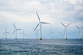 Nine wind turbines at sea. Windmills in blue ocean with a clouded blue sky.