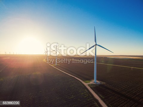 Sun rises on row of wind turbines. The sky is clear and blue.