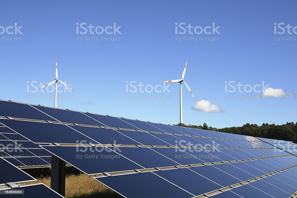Wind turbines behind field of solar panels under clear sky royalty-free stock photo