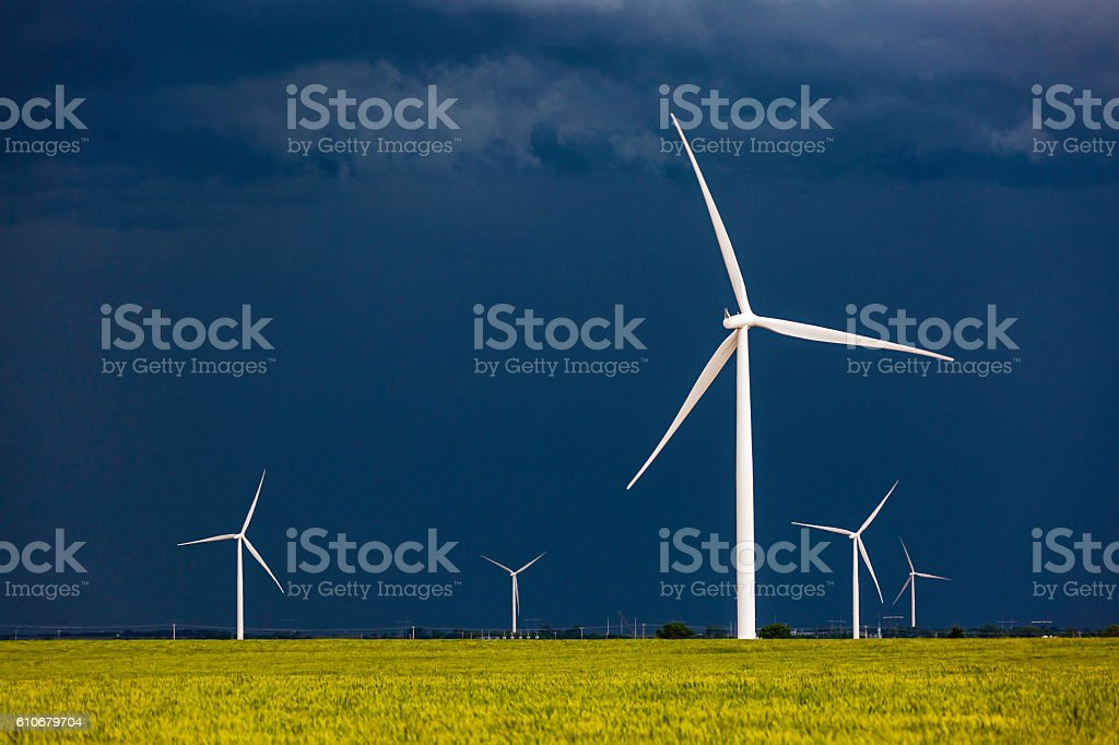 Wind turbines contrast with dark stormy sky and yellow crop stock photo