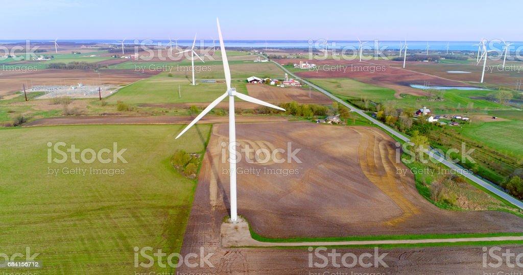 Vindkraftverk dominerar jordbrukslandskapet, dwarfing gårdar och silos. royaltyfri bildbanksbilder