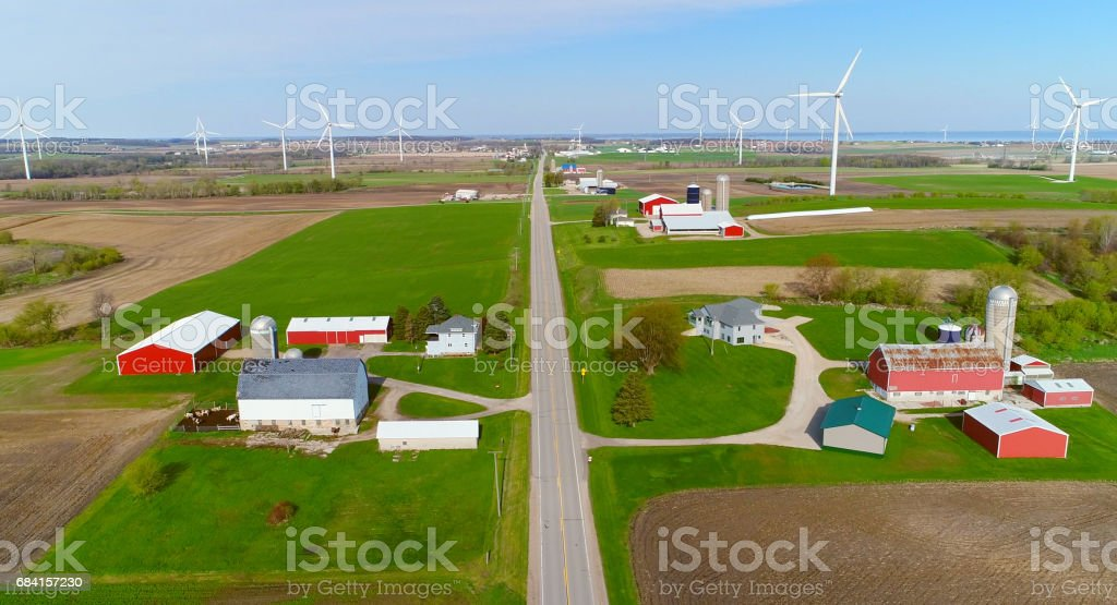 Wind turbines dominate the landscape, dwarfing farms and trees. Wind turbines dominate the agricultural landscape, dwarfing farms and silos. foto stock royalty-free