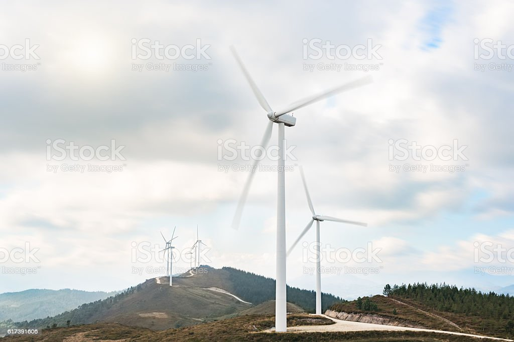 Wind turbines farm in eolic park generating energy with air stock photo