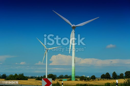 Windmill turbines with partially cloudy blue sky in the background. Wind turbines for renewable energies