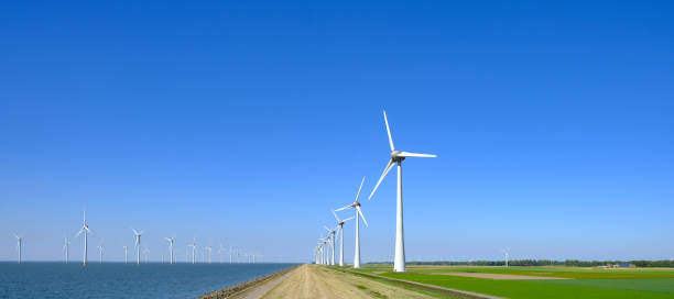 Wind turbines in a windpark on the shore of a lake in The Netherlands stock photo