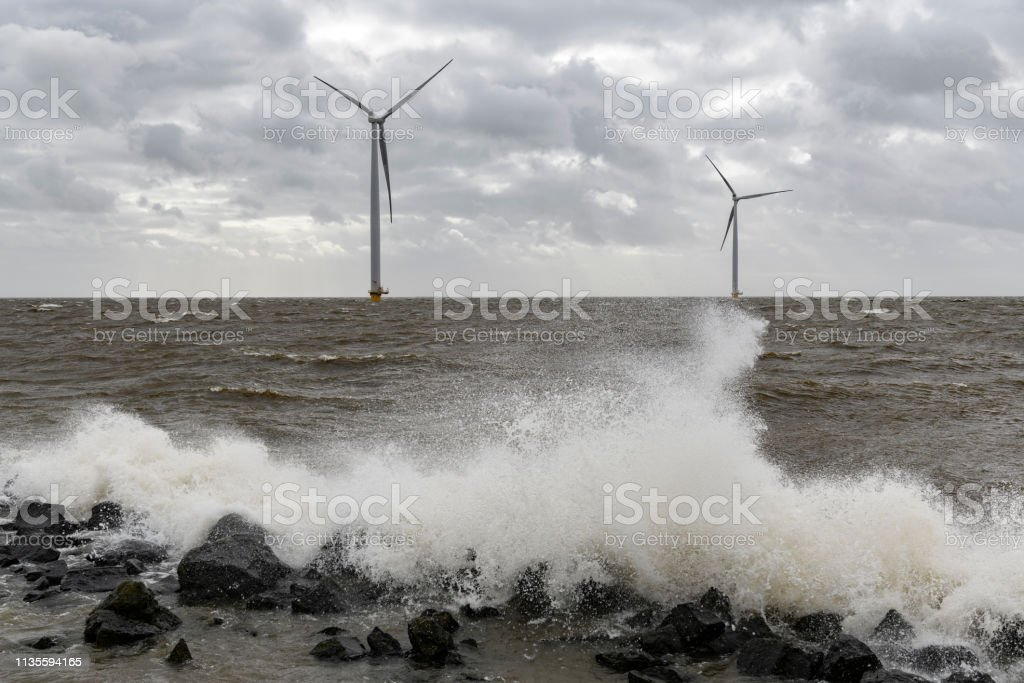 Wind turbines in an offshore wind park during a storm with big waves...