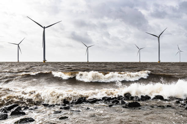 Wind turbines in an offshore wind park during a storm with big waves hitting the shore stock photo