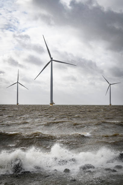 Wind turbines in an offshore wind park during a storm with big waves hitting the shore - foto stock