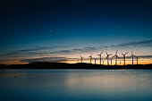 Windmills in the sunset. Wind turbines motion landscape at sunset with plane in background
