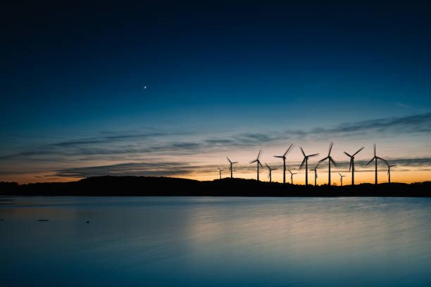 Wind turbines motion landscape sunset Windmills in the sunset. Wind turbines motion landscape at sunset with plane in background windmill stock pictures, royalty-free photos & images