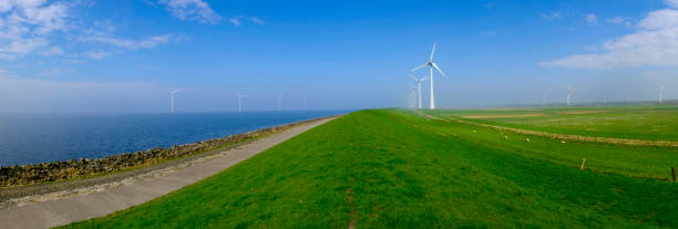 Wind turbines on a levee in a windpark during a calm day stock photo