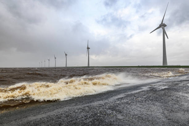 Wind turbines on land and offshore in a storm stock photo