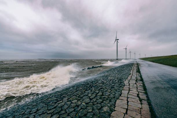 Wind turbines on land and offshore in a storm with waves hitting a levee stock photo