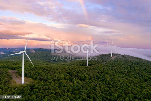 Aerial view of wind turbines taken with a drone in Vermont. Pink clouds and rainbow in background.